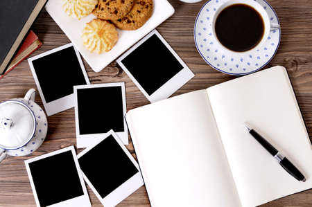 Photo album on a wood table with several blank instant camera photo prints, coffee and biscuits.  Space for copy. 스톡 콘텐츠