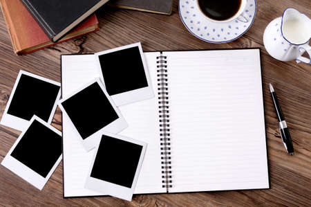 Photo album on a wood table with several blank instant camera photo prints, coffee and books.  Space for copy. photo