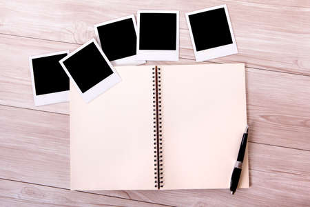 Photo album on a gray wood surface with several blank instant camera photo prints.  Space for copy. photo