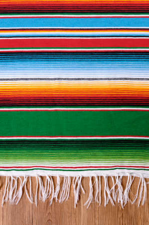 Mexican background with traditional serape blanket or rug on a wood floor.  Space for copy. Banco de Imagens