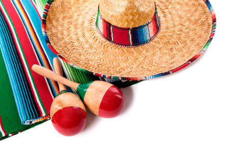 mexican background: Traditional Mexican serape blanketor rug with sombrero and maracas isolated against a white background.  Space for copy.