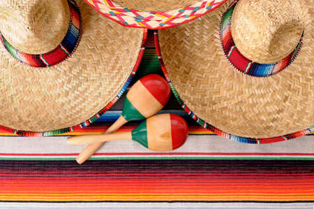 serape: Mexican scene with sombrero straw hat, maracas and traditional serape blanket or rug.  Space for copy. Stock Photo