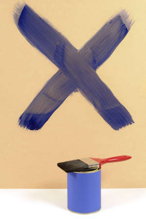 paint can: Blue cross or letter X painted on a wood wall with paint can and paintbrush.