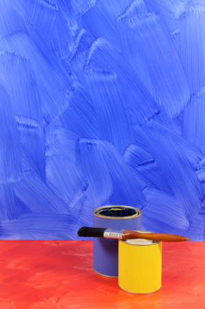 intentionally: Blue painted wall with red floor and selection of paints (please note that the painted wall and floor have intentionally visible brushstrokes).
