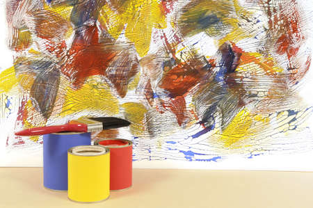 redecorating: Partly finished untidy or messy painted wall with paint cans and paintbrushes. Space for copy.