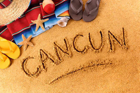 cancun: The word Cancun written in sand on a Mexican beach, with sombrero, straw hat, traditional serape blanket, starfish and maracas. Stock Photo