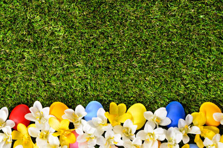 flower bed: Easter background with hand painted eggs hidden in flowers with copyspace.