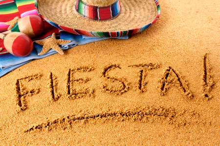 The word Fiesta written in sand on a Mexican beach, with sombrero, straw hat, traditional serape blanket, starfish and maracas. Banco de Imagens