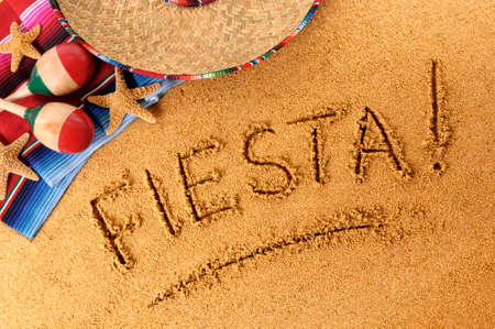 serape: The word Fiesta written in sand on a Mexican beach, with sombrero, straw hat, traditional serape blanket, starfish and maracas. Stock Photo