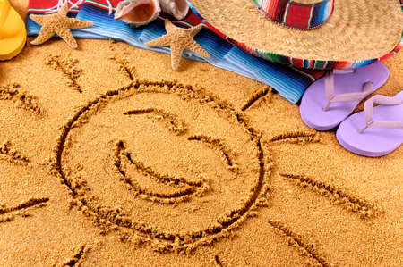 serape: Smiling sun drawn in sand on a Mexican beach, with sombrero, straw hat, traditional serape blanket, starfish and seashells. Stock Photo