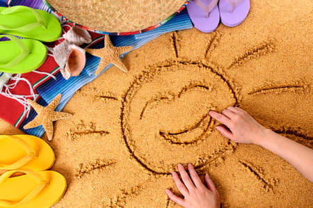 serape: Child drawing a smiling sun in sand on a Mexican beach, with sombrero, straw hat, traditional serape blanket, starfish and seashells.