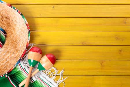 멕시코 챙 넓은 모자, 마라카스와 노란색 페인트 소나무 나무 바닥에 누워 전통적인 serape 담요. 복사를위한 공간입니다. 스톡 콘텐츠