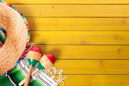 sombrero: Mexican sombrero, maracas and traditional serape blanket laid on a yellow painted pine wood floor.  Space for copy. Stock Photo