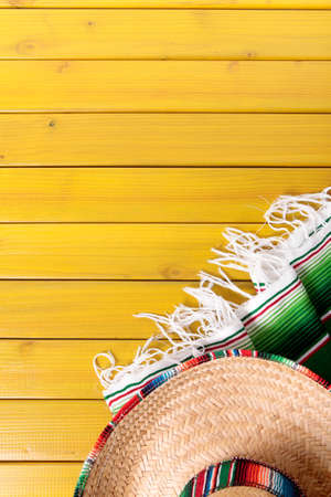 Mexican sombrero and traditional serape blanket laid on a yellow painted pine wood floor.  Space for copy. Stock Photo