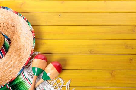 chapeau de paille: Sombrero mexicain, maracas et une couverture de serape traditionnelle posé sur un plancher de bois peint de pin jaune.