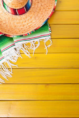 Mexican sombrero and traditional serape blanket laid on a yellow painted pine wood floor.  Space for copy. Banco de Imagens