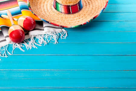 Mexican sombrero and maracas with traditional serape blanket laid on an old blue painted pine wood floor.  Space for copy. Banco de Imagens
