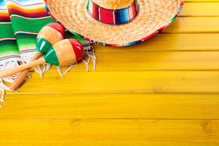 serape: Mexican sombrero, maracas and traditional serape blanket laid on a yellow painted pine wood floor.  Space for copy. Stock Photo