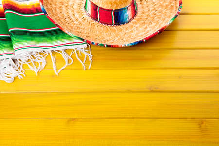serape: Mexican sombrero and traditional serape blanket laid on a yellow painted pine wood floor.  Space for copy. Stock Photo