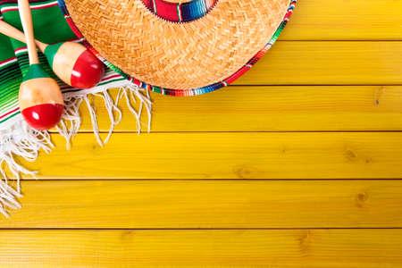 sombrero de charro: Sombrero mexicano, maracas y una manta sarape tradicional establecido en un piso de madera de pino pintada de amarillo. Espacio para la copia.