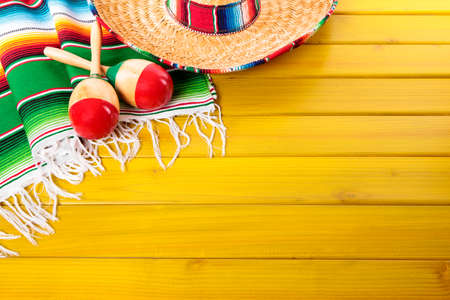 Mexican sombrero, maracas and traditional serape blanket laid on a yellow painted pine wood floor.