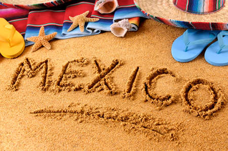 serape: The word Mexico written in sand on a Mexican beach, with sombrero, straw hat, traditional serape blanket, starfish and seashells.