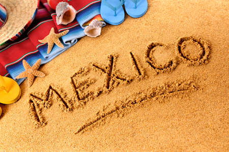 serape: The word Mexico written in sand on a Mexican beach, with sombrero straw hat, traditional serape blanket, starfish and seashells.