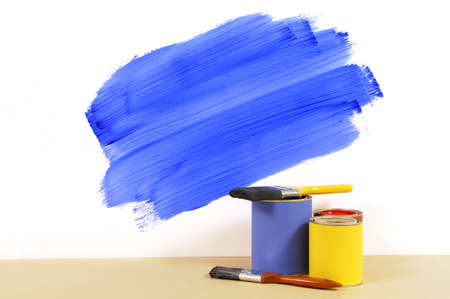 redecorating: Partly finished blue painted wall with paint can and paintbrushes.  Space for copy.