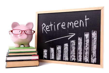 Pink piggy bank with glasses standing on books next to a blackboard with retirement savings chart.  Sharp focus on the piggy bank.