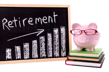 Pink piggy bank with glasses standing on books next to a blackboard with retirement savings chart.  Sharp focus on the piggy bank. photo