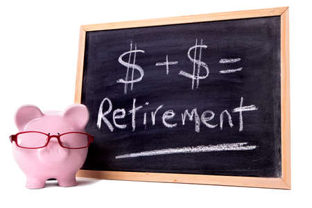 Pink piggy bank with glasses standing next to a blackboard with simple retirement calculation.  Sharp focus on the piggy bank. photo