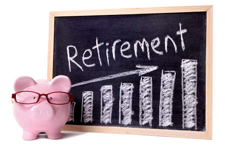 Pink piggy bank with glasses standing next to a blackboard with retirement savings message.  Sharp focus on the piggy bank. photo