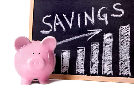 Pink piggy bank standing next to a blackboard with savings growth chart.  Sharp focus on the piggy bank.