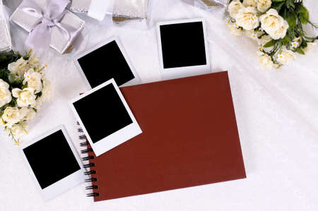 photo album book: Red photo album with blank instant photo prints laid on bridal lace with several silver wedding gifts and white rose bouquets.  Space for copy.
