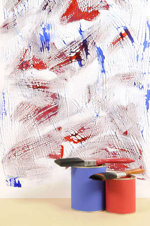 untidy: Partly finished untidy or messy blue and red painted wall with paint cans and paintbrushes. Space for copy.