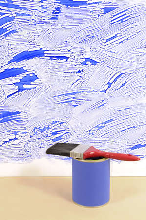 untidy: Partly finished untidy or messy blue painted wall with paint can and paintbrush. Space for copy.