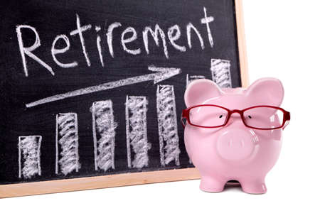 은퇴 저축 메시지와 함께 칠판 옆에 서있는 안경 핑크 돼지 저금통. 돼지 저금통에 날카로운 초점. 스톡 콘텐츠