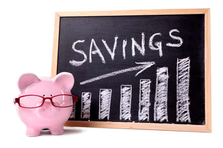 Pink piggy bank with glasses standing next to a blackboard with savings growth chart.  Sharp focus on the piggy bank. photo