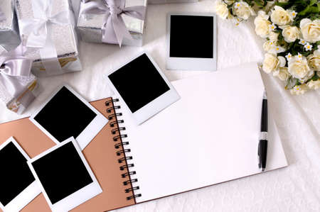 photo album book: Photo album with blank instant photo prints laid on bridal lace with several silver wedding gifts and white rose bouquet.  Space for copy.