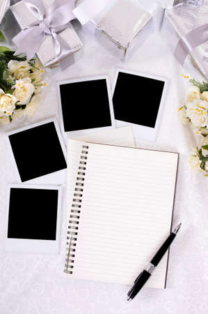 photo album book: Wedding album with blank instant photo prints laid on bridal lace with several silver gifts and rose bouquets.  Space for copy.