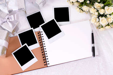 Photo album with blank instant photo prints laid on bridal lace with several silver wedding gifts and white rose bouquet.  Space for copy.