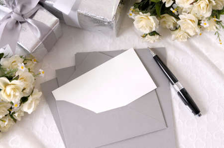 Writing paper or wedding invitation with envelope laid on bridal lace with several wedding gifts and white rose bouquets.  Space for copy. Stockfoto