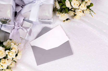 Blank invitation or thank you card with several wedding gifts and white rose bouquet laid on bridal lace.  Space for copy. 스톡 콘텐츠