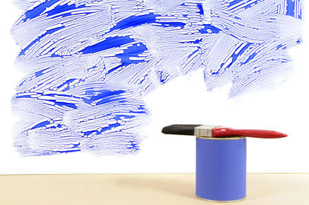 redecorating: Partly finished untidy or messy blue painted wall with paint can and paintbrush. Space for copy.
