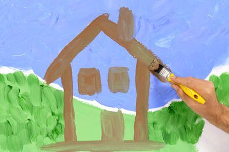 home decorating: Home decorating concept with man painting a house scene on a white wall.   Space for copy.