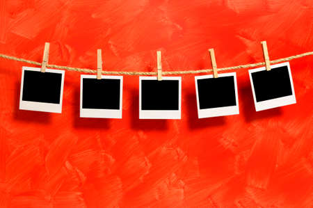 Several blank instant camera photo prints hanging on a rope or washing line isolated against a painted red wall background.  Space for copy.
