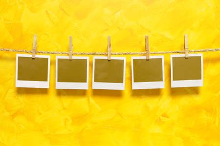 Several blank instant camera photo prints hanging on a rope or washing line isolated against a painted yellow wall background.  Space for copy. photo