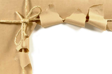 Brown paper parcel or package tied with string and torn open in an untidy manner isolated on a white background.  Space for copy. 스톡 콘텐츠