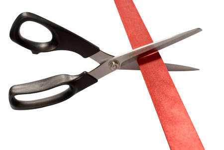 commencing: Close-up of scissors cutting red ribbon or tape isolated on a white background Stock Photo