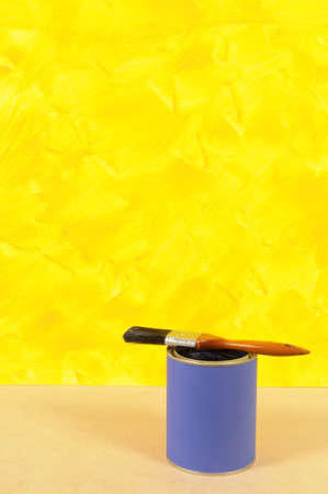 paint can: Partly finished blank yellow painted wall with paint can and paintbrush.  Space for copy. Stock Photo